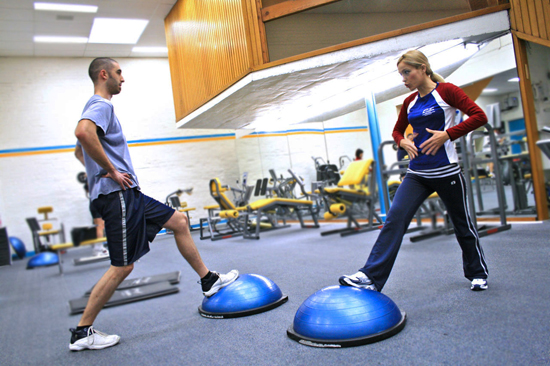A personal trainer demonstrating proper exercise procedure; photo courtesy LocalFitness.com